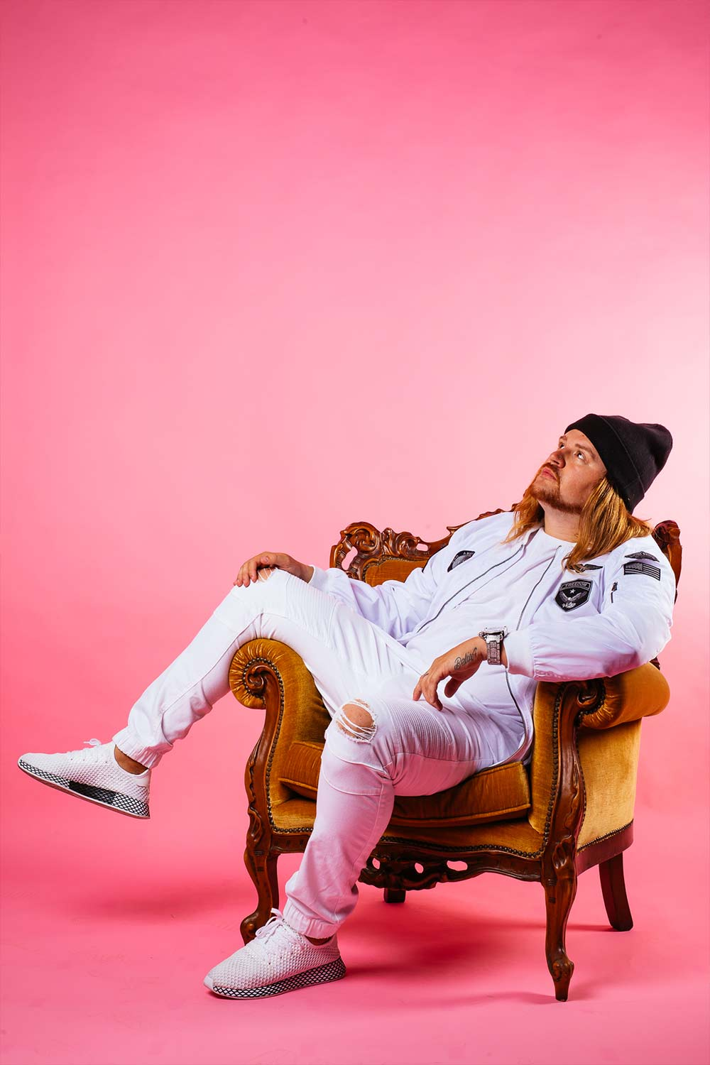 Male artists sitting for a portfolio photo on a pink background